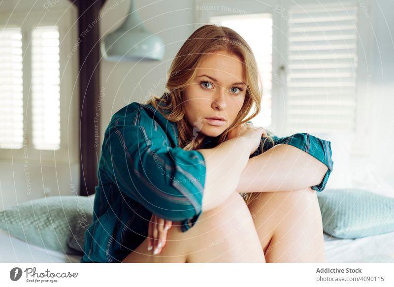 Junge Frau sitzt auf dem Bett Hände auf den Knien jung Freude heiter schön attraktiv hübsch charmant sinnlich cool verführerisch traumhaft einladend schlank