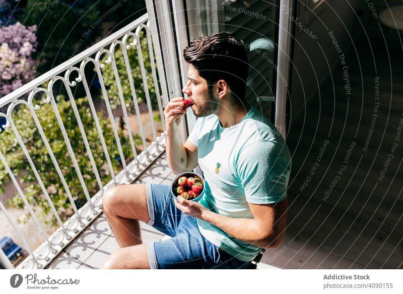 Junge glücklich sexy männlich essen Erdbeere in der Nähe von Terrasse Mann Essen Erdbeeren Schalen & Schüsseln Glück Unterwäsche Balkon jung Freude heiter