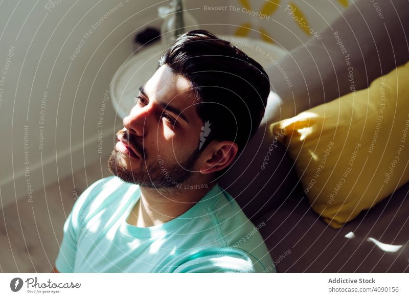 Junge traurige Mann sitzt auf Couch zu Hause einsam müde Ausdruck Sofa Liege jung männlich deprimiert gestresst überdrüssig allein ernst gutaussehend gelungen