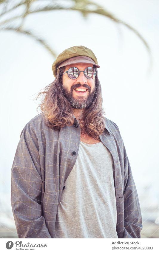 stilvollen bärtigen Mann mit langen Haaren zu Fuß auf der Straße mit Sonnenbrille trendy Schnurrbart Porträt Typ Blick Behaarung cool stylisch gutaussehend