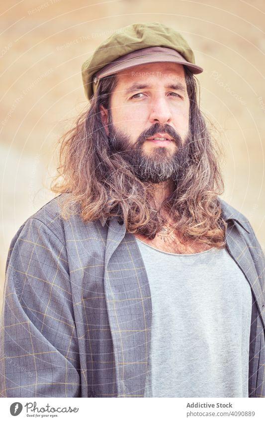 stilvollen bärtigen Mann mit langen Haaren auf der Straße posieren und Blick auf die Kamera trendy Schnurrbart Sonnenbrille Porträt Typ Behaarung cool stylisch