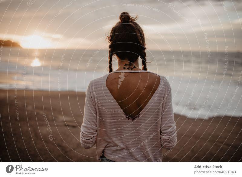 Anonyme weibliche stehend in Richtung winken Meer auf Sonnenuntergang Frau Stehen Strand MEER Wellen Abend jung Sommer Urlaub Wasser Unwetter Natur Landschaft