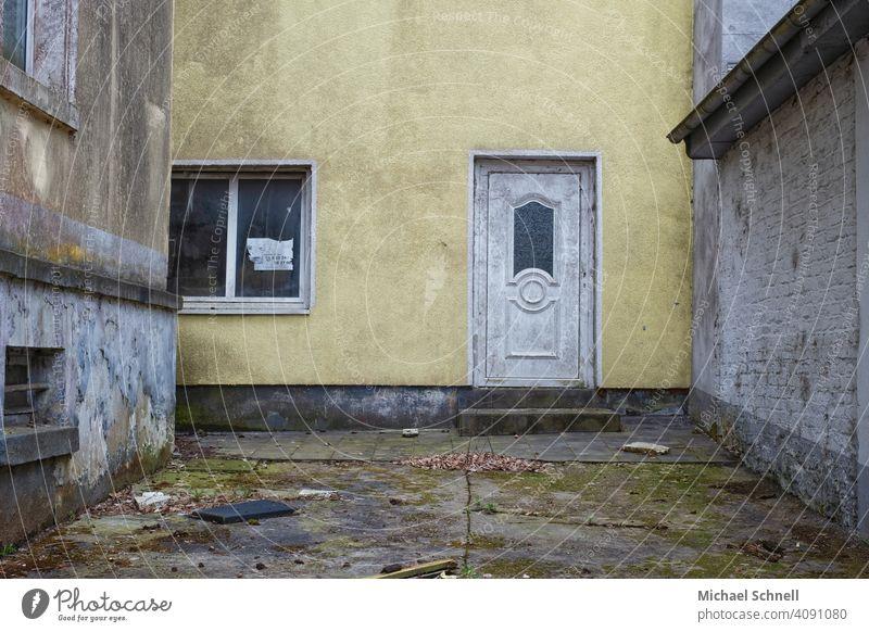 Innenhof eines verlassenen Hauses Architektur Gebäude dreckig verfallen alt trist gelb Menschenleer Fassade Farbfoto Wand Vergänglichkeit Tür Eingang Leerstand