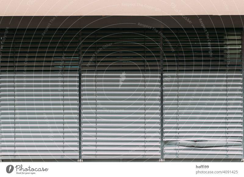 Die verdellte Lamelle der geschlossenen Jalousie. Delle Jalousien kaputt kaputte Jalousie Rollo Schatten Rollladen Fassade Strukturen & Formen Gebäude Fenster