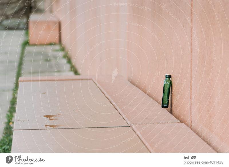 ein leerer Grüner Flachmann auf einer rosa Sitzbank Alkohol Alkoholsucht Schnapsflasche ausgetrunken Spirituosen Flasche Glas trinken Getränk Sucht Rauschmittel