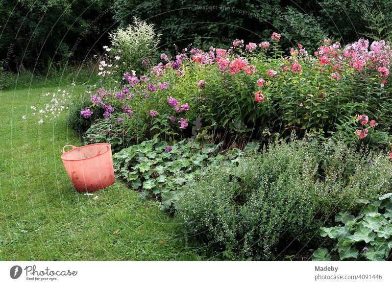 Bauerngarten mit vielen bunten Sommerblumen und rotem Gartenkorb aus Plastik im Sommer in Rudersau bei Rottenbuch im Kreis Weilheim-Schongau in Oberbayern Korb