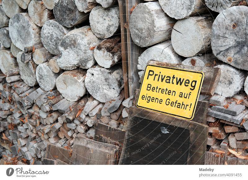 Gelbes Blechschild mit Warnhinweis vor gestapeltem Brennholz vor einem alten Bauernhaus im Herbst in Rudersau bei Rottenbuch im Kreis Weilheim-Schongau in Oberbayern