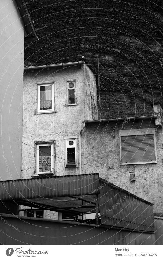 Verwahrlostes Wohnhaus mit alten Gardinen und heruntergelassenem Rollladen im Mathildenviertel in Frankfurt am Main in Hessen, fotografiert in neorealistischem Schwarzweiß