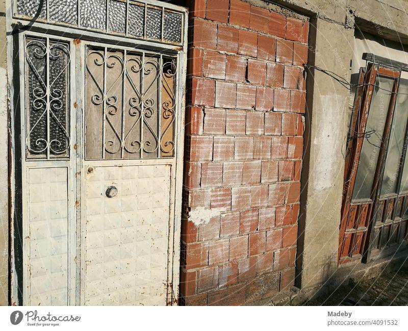 Alte leerstehende Werkstatt mit Tür aus Schmiedeeisen und unverputztem Backstein im Sonnenschein in Alacati bei Cesme am Mittelmeer in der Provinz Izmir in der Türkei