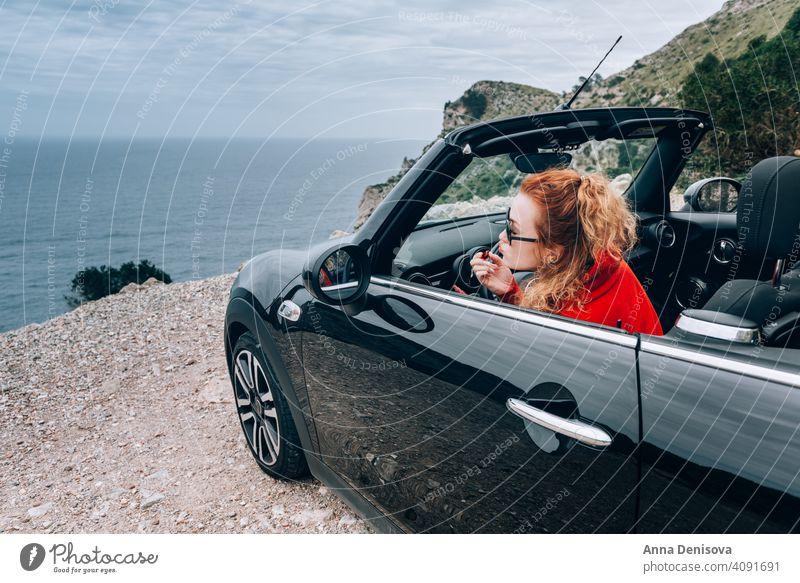 Junge Frau im Cabrio Cabriolet PKW jung Frau im Auto Glanz Lippenstift Glück attraktiv Sommer Urlaub Miete Lifestyle offenes Dach gefaltet rot Ausflug fahren