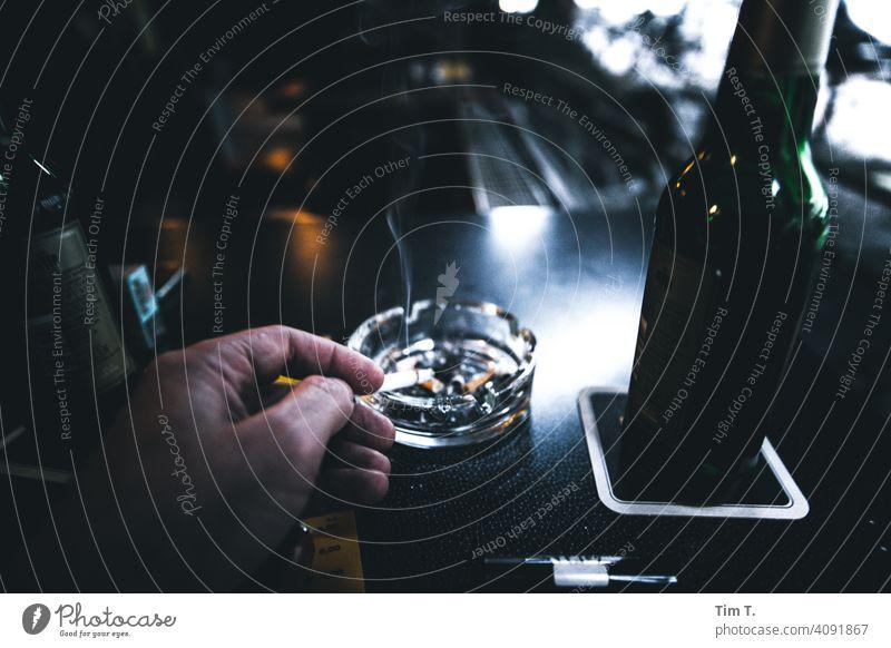 Kneipe Hand Aschenbecher Bier Innenaufnahme Flasche Gastronomie Alkohol Getränk trinken Rauchen Zigarette Farbfoto genießen Mann Bar Tisch Mensch Durst