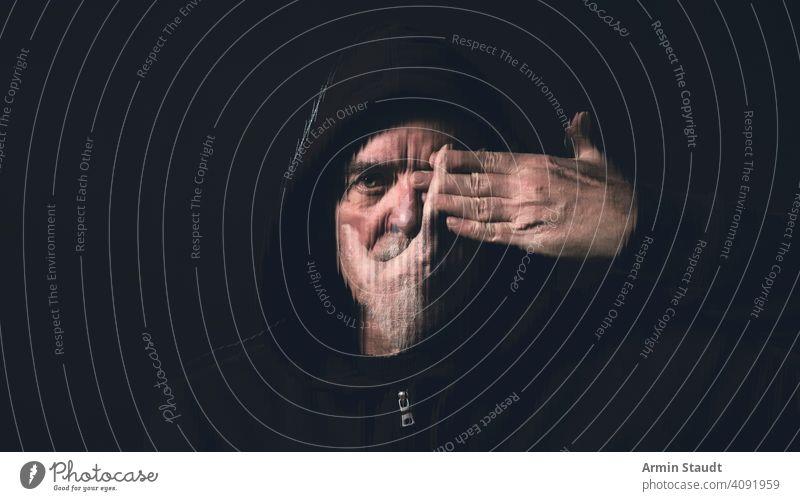 Porträt eines Mannes mit Kapuzenpulli, der eine Hand vor sein Gesicht hält alt Vollbart verdoppeln Belichtung streifen Hände Auge Mund stumm blind Atelier