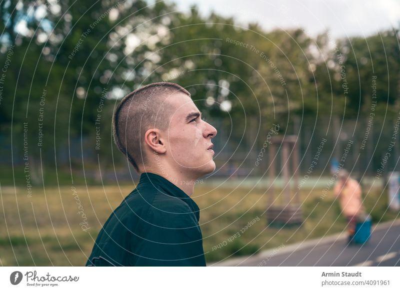 Porträt im Profil eines ernsten jungen Mannes auf der Straße Teenager Blick männlich schön lässig Kaukasier im Freien selbstbewusst Model Lifestyle Reise