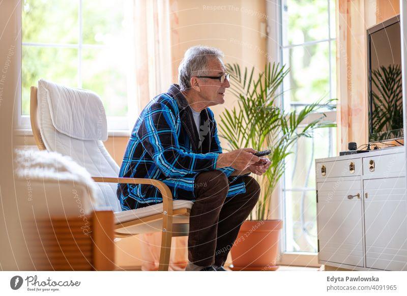 Senior Mann mit TV-Fernbedienung älter Großvater alt Rentnerin in den Ruhestand getreten gealtert reif heimwärts Haus männlich Menschen Lifestyle