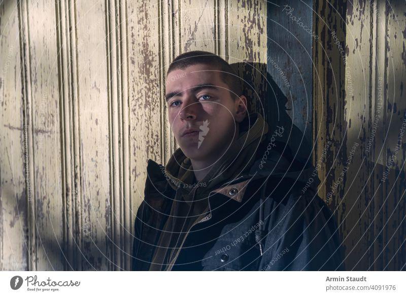 Porträt eines ernsten jungen Mannes, der an einer alten Holzwand lehnt Wand Farbe angeblättert Grunge Kapuzenpulli cool trendy Schatten dunkel geheimnisvoll