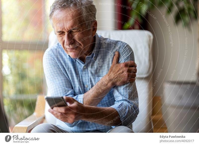 Älterer Mann erleidet Schmerzen bei der Nutzung eines Smartphones zu Hause Senior älter Großvater alt Rentnerin in den Ruhestand getreten gealtert reif
