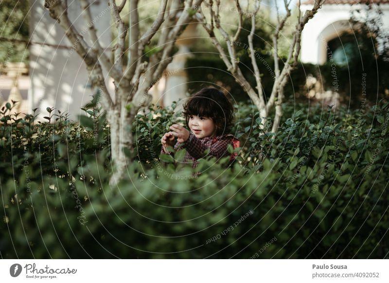 Kind spielt im Park Kindheit authentisch Mädchen 1-3 Jahre Kaukasier Lifestyle Tag Freude Kindheitserinnerung Farbfoto Mensch Sträucher grün Frühling