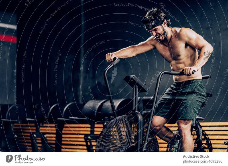 Fleißiger Mann trainiert auf dem Gymnastikrad Fitnessstudio Training Heimtrainer fleißig stark männlich Zeitgenosse Sportverein Übung aktiv muskulös sportlich