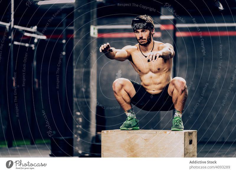 Athletischer Mann springt auf einen Kasten, um seine Ausdauer im Fitnessstudio zu verbessern Trainerin Training muskulös springend Übung sportlich Klient