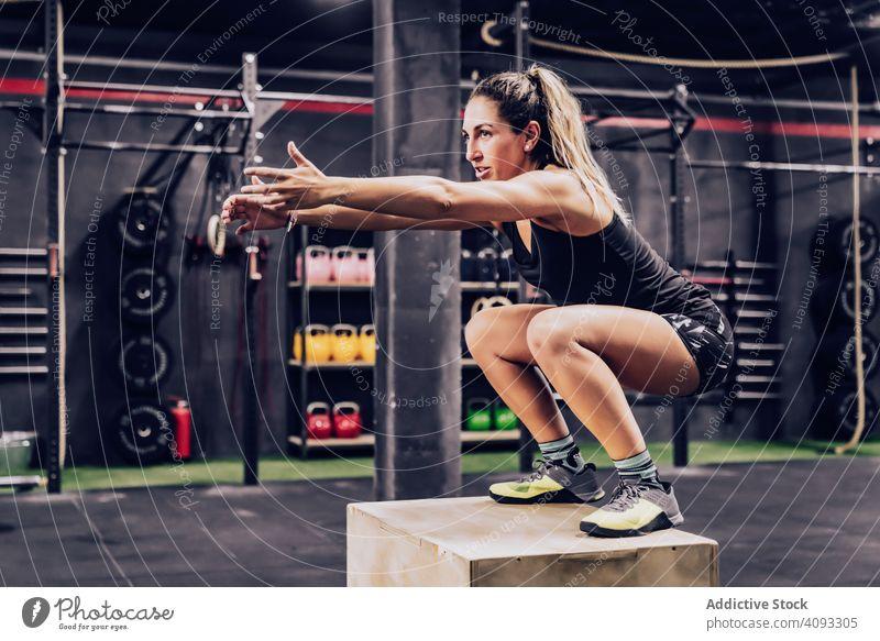 Sportliche Frau springt auf einen Kasten, um ihre Ausdauer im Fitnessstudio zu verbessern Trainerin Training muskulös springend Übung sportlich Klient