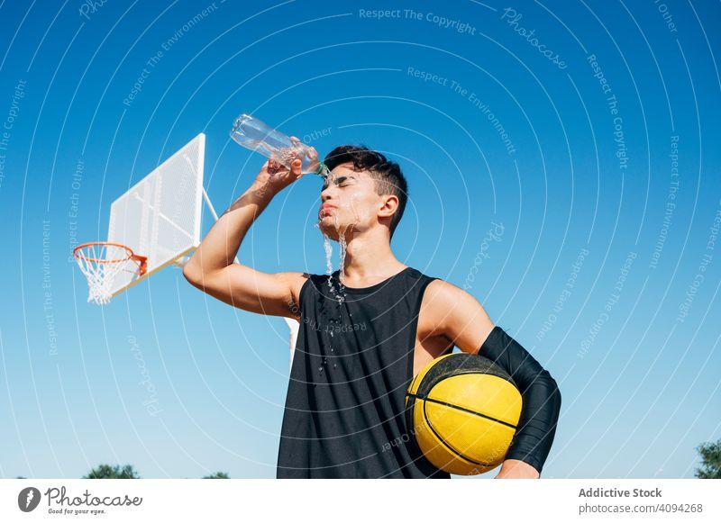 Junger Mann steht mit Ball und spielt auf Basketballplatz im Freien. Athlet Konkurrenz Sportgerät Erwachsener Erholung Aktion Porträt aktiv Aktivität Asphalt