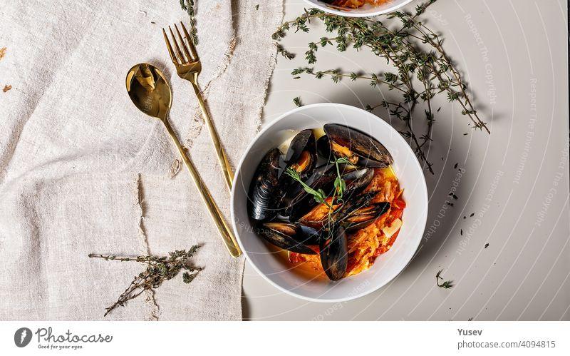 Lebensmittel-Banner. Eine Portion Muscheln mit Gemüse in einer weißen Schüssel auf einem hellen Hintergrund. Leckere und gesunde Meeresfrüchte. Schalentiere. Ansicht von oben