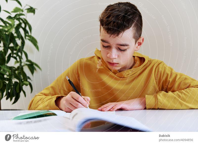 Teenager Junge schreiben Hausaufgaben zu Hause. Bildung Konzept Schule schreibend heimwärts studierend Buch Person Schüler Menschen Kindheit Kaukasier