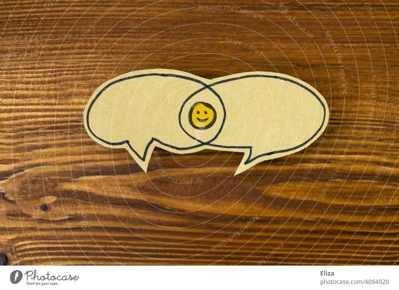 Zwei Sprechblasen mit einer Schnittmenge in der sich ein lachender Smiley befindet. Positive Kommunikation, Konsens und Einigkeit. Lösung positiv sprechen