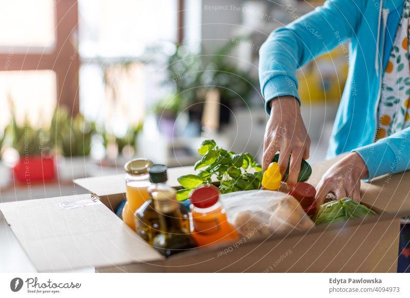 Frau beim Auspacken einer Kiste mit Lebensmitteln zu Hause Supermarkt Markt Laden Frucht Gemüse Gesundheit Lebensmittelgeschäft organisch frisch Küche Diät