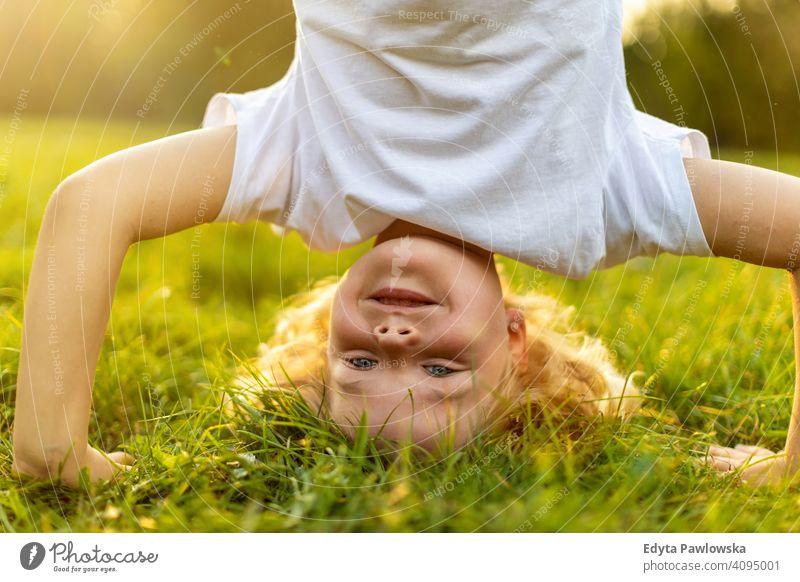 Kind macht Kopfstand im Park Handstand auf den Kopf gestellt trainiert. Sport Gesundheit Vitalität aktiv Menschen Junge kleiner Junge Kinder Kindheit im Freien