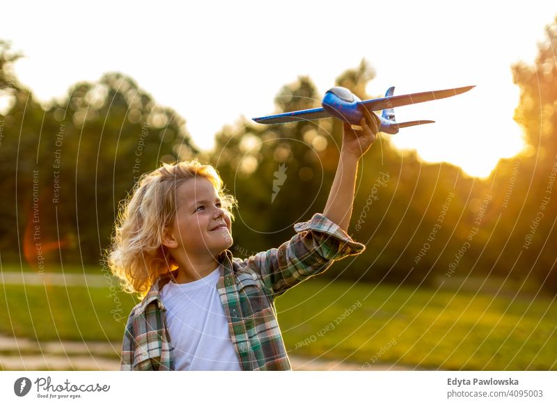 Kleiner Junge spielt mit Spielzeug Flugzeug im Park Menschen Kind kleiner Junge Kinder Kindheit im Freien lässig niedlich schön Porträt Lifestyle elementar