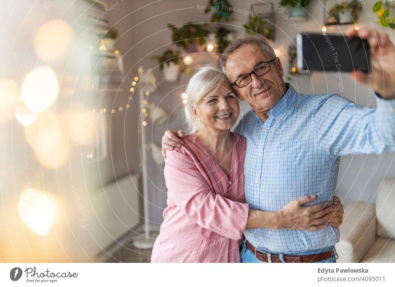 Senior Paar im Wohnzimmer nehmen Selfie mit Smartphone Menschen Frau Erwachsener reif lässig attraktiv männlich Mann Lächeln Glück Kaukasier zahnfarben