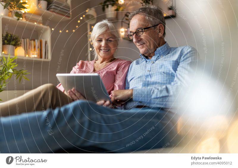 Reifes Paar verwendet ein Tablet beim Entspannen zu Hause Menschen Frau Erwachsener Senior reif lässig attraktiv männlich Mann Lächeln Glück Kaukasier