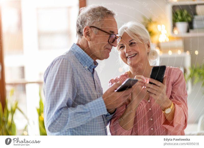 Älteres Ehepaar benutzt Mobiltelefone zu Hause Menschen Frau Erwachsener Senior reif lässig attraktiv männlich Mann Lächeln Glück Kaukasier zahnfarben genießend