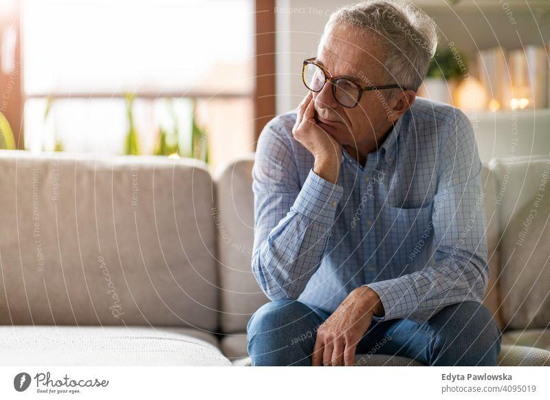 Besorgter älterer Mann sitzt allein in seinem Haus Menschen eine Person Senior reif Rentnerinnen in den Ruhestand getreten alt graues Haar Kaukasier Erwachsener
