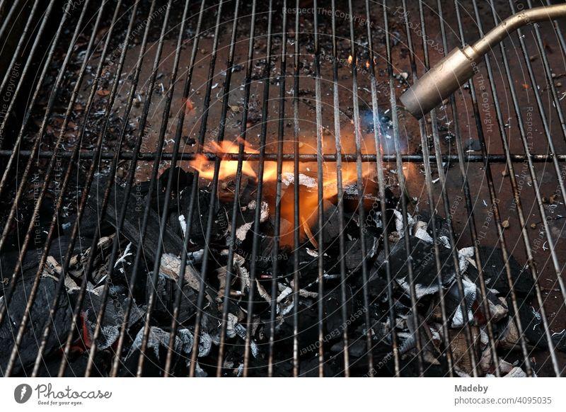 Gasflamme eines Schweißgerät zum anheizen der Glut eines Holzkohlegrill bei einem Barbecue in Rudersau bei Rottenbuch im Kreis Weilheim-Schongau in Oberbayern