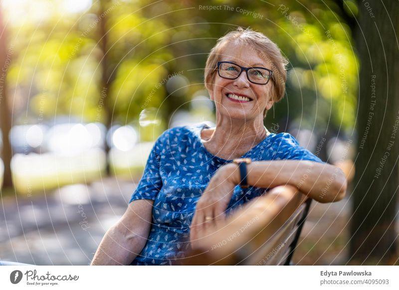Porträt einer glücklichen älteren Frau, die auf einer Bank sitzt Menschen Senior reif lässig Kaukasier alt Großmutter Rentnerin Großeltern