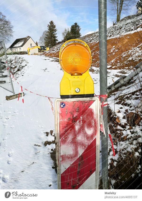 Warnbake mit rotem Graffiti und gelber Blinkleuchte im Winter mit Schnee auf einer Baustelle in Oerlinghausen bei Bielefeld am Hermannsweg im Teutoburger Wald in Ostwestfalen-Lippe