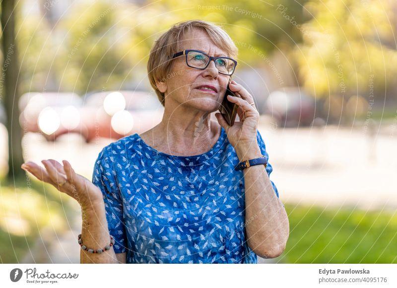 Gestresste ältere Frau, die im Freien ein Mobiltelefon benutzt Menschen Senior reif lässig Kaukasier alt Großmutter Rentnerin Großeltern