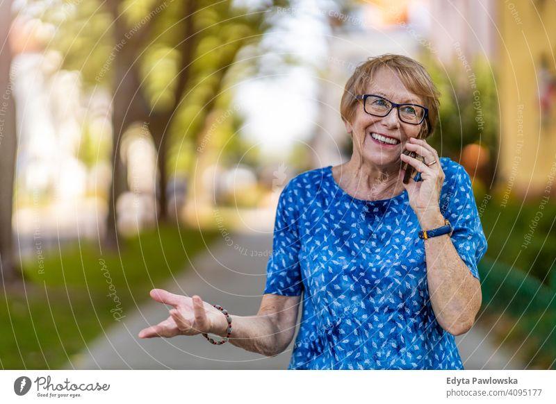 Porträt einer älteren Frau, die ein Mobiltelefon im Freien benutzt Menschen Senior reif lässig Kaukasier alt Großmutter Rentnerin Großeltern