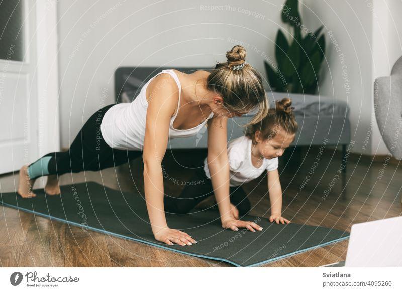 Eine junge sportliche Mutter und ein Mädchen machen zusammen Übungen zu Hause. Gesunde Entwicklung von Eltern und Kindern, gesunder Lebensstil Frau Fitness