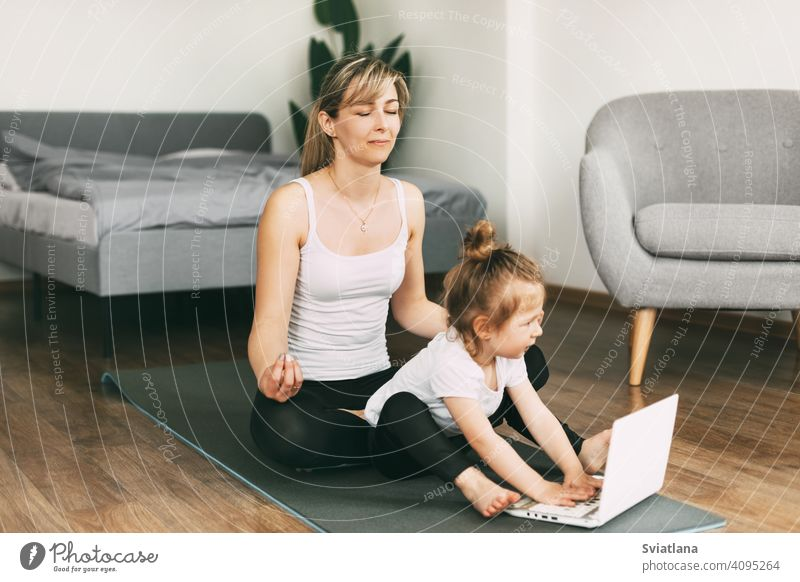 Eine schöne junge Frau und ihre bezaubernde kleine Tochter lächeln und meditieren nach einem gemeinsamen Workout Yoga Mama Meditation heimwärts Zusammensein