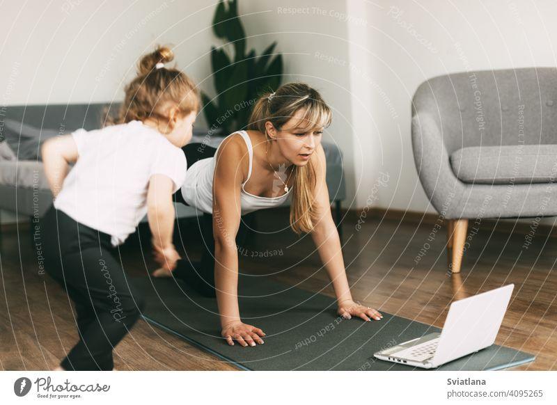 Eine junge Mutter treibt zu Hause Sport und schaut sich eine Video-Fitnessstunde auf einem Laptop an, und ihr kleines Baby sitzt auf einem Stuhl. Heimtraining, Fitness, Sport