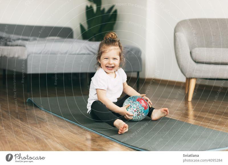 Ein kleines Kind spielt auf einer Sportmatte mit einem Ball Unterlage Gesundheit Baby Mädchen Kaukasier Spaß Kindheit Glück niedlich Lächeln Fitness Kleinkind