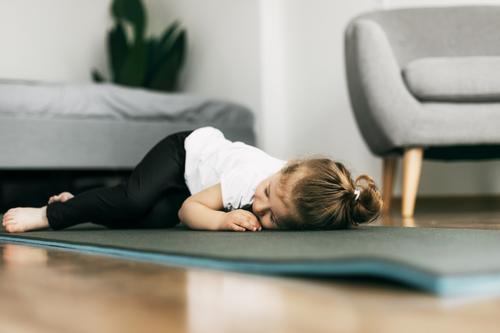 Ein kleines Mädchen liegt auf einer Yogamatte im Schlafzimmer und ruht sich nach einem Spiel aus Baby Glück Lügen Unterlage Stock spielen Kind niedlich