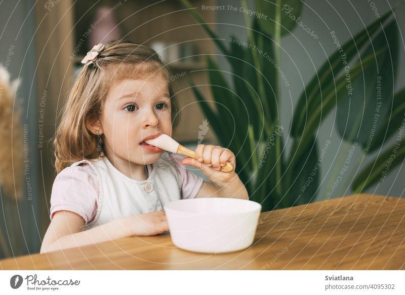 Ein kleines Mädchen isst Brei aus einer weißen Schüssel, ein Mädchen frühstückt am Tisch sitzend. Gesundes Frühstück, gesundes Essen Gesundheit Kind Haferbrei