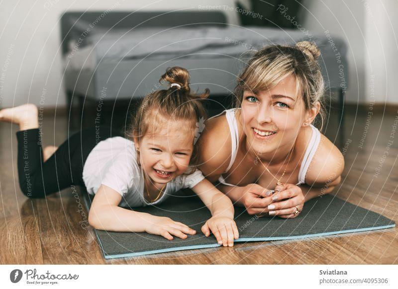 Eine schöne junge Frau und ein bezauberndes kleines Mädchen schauen in die Kamera und lächeln, während sie auf einer Yogamatte im Schlafzimmer liegen Fitness