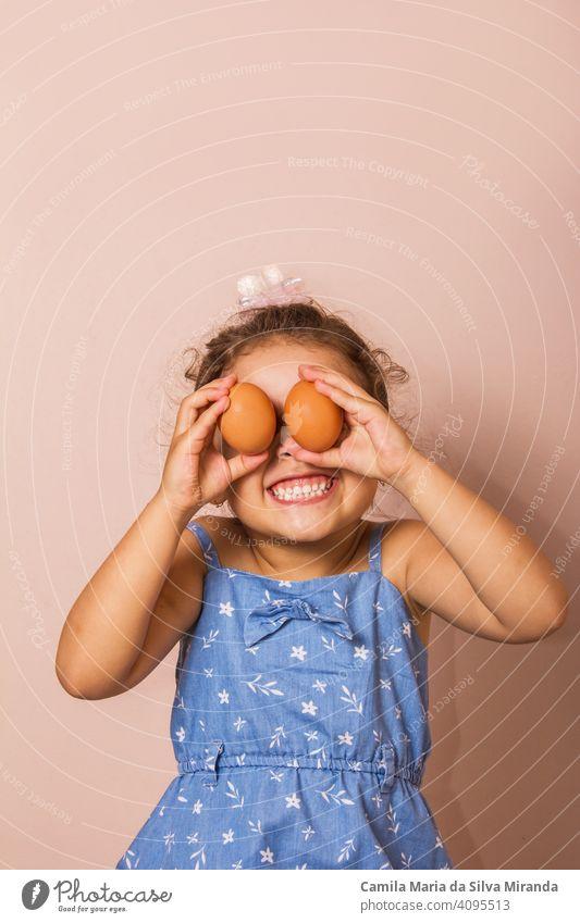 Lächelndes Kind hält zwei Eier. Hintergrund schön Hase Kaukasier feiern Feier farbenfroh Textfreiraum niedlich Ohren Ostern Spaß lustig Mädchen Glück Feiertag