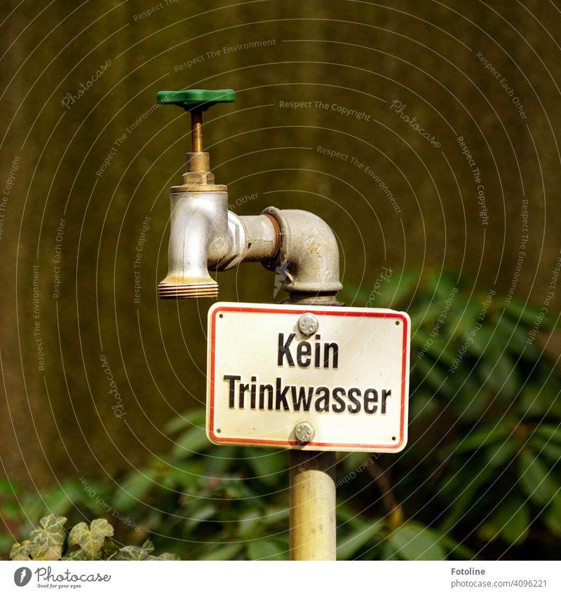 """""""Kein Trinkwasser"""" steht direkt unter dem alten Wasserhahn Rad Metall Eisen Eisenrohr Rost Menschenleer Außenaufnahme Nahaufnahme Detailaufnahme Tag Farbfoto"""