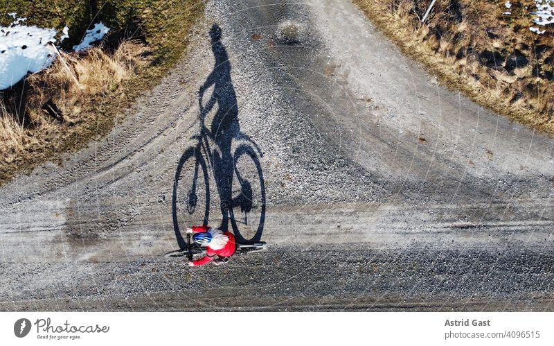 Luftaufnahme mit einer Drohne von einer Fahrradfahrerin auf einer Straße mit Schatten luftaufnahme drohnenfoto frühling sport radfahren fahrrad frau